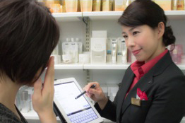 An in-store beauty consultant with a B-TAB helping a consumer